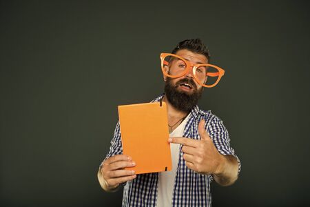 Look at this book. Bearded man in party glasses pointing at lesson book. Study nerd holding book. Book nerd wearing fancy glasses. University male student with lecture notes