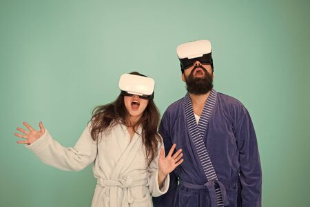 Future life. Good morning. Couple in love. Family. Virtual reality. Love. Happy family in vr glasses. Bearded man and woman in robe pajama. Future is now. Future technology. Vr glasses is our future 写真素材
