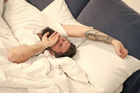Relax and sleep concept. Man bearded guy sleep on white sheets. Healthy sleep and wellbeing. Man bearded hipster sleepy in bed. Early morning hours. Insomnia and sleep problems. Lets start new day
