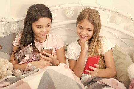Have a great and blessed holiday. Texting Christmas and New Year greetings by phone. Happy small children with mobile phone. Small girls use smartphone in bed. Merry Christmas and Happy New Year