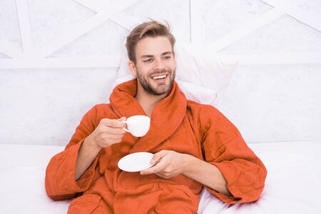 Starting day with good coffee. Relaxing at home. Pleasant moments. Gourmet espresso. Enjoy morning coffee. Happy morning. Handsome man drink morning coffee. Happy bearded man in bed. Good mood 写真素材