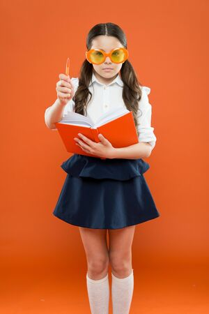 inspiration for writing. get information from book. happy school girl in uniform and party glasses. small child with notebook. literature lesson education. writing in workbook. children literature
