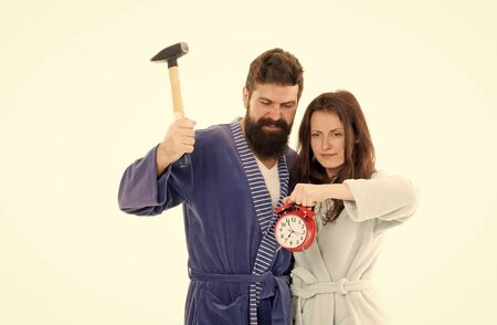 Early morning anxiety. Lets get rid of this annoying alarm clock. Couple in bathrobes going to destroy alarm clock and stay at home. Breaking rules. Man with hammer beat alarm clock. Hateful sound 写真素材