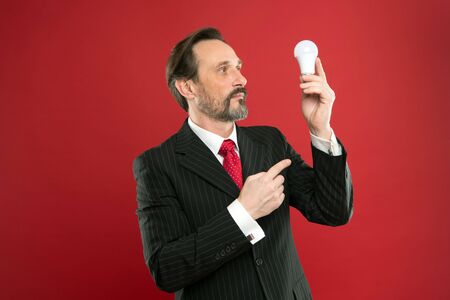 Man mature well groomed bearded businessman formal suit hold light bulb red background. Symbol of idea progress and innovation. Idea for business. Inspiring idea. Inspiration for business copy space Stockfoto