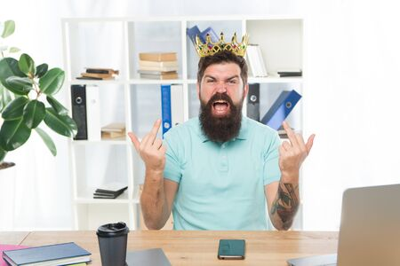 Hate you. Aggressive boss shouting show middle finger gesture. Man arrogant rude boss with golden crown sit in office. Superiority and self confidence. King of office. Serious boss at work place