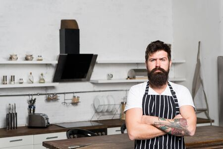 Best chef ever. bearded man hipster in kitchen. brutal man in cook apron. mature male with beard cooking. culinary business. tasty cuisine. serious and confident chef in restaurant. Culinary expert Reklamní fotografie