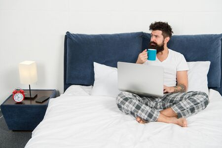 Hipster bearded guy pajamas freelance worker. Remote work concept. Social networks internet addiction. Online shopping. Man surfing internet or work online. Just woke up and already at work Archivio Fotografico