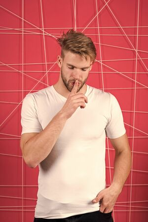 Guy bearded attractive shows silence gesture. Secret concept. Man with beard unshaven guy looks handsome well groomed and dreamy. Man with bristle strict calm mysterious face, pink background