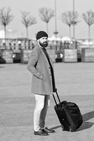 Man bearded hipster travel with big luggage bag on wheels. Let travel begin. Traveler with suitcase waiting transportation to airport railway station. Ready to travel. Carry travel bag. Business trip 版權商用圖片