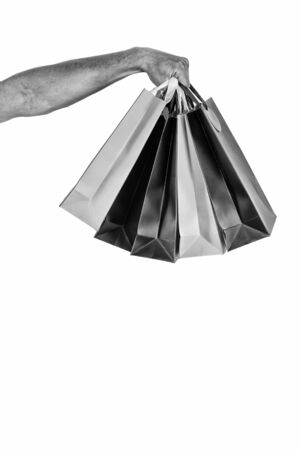 Shopping bags in hand isolated white background. Paper bags packages. Shopping and package concept. Holidays preparation shopping. Bunch of shopping bags in male hand copy space Stok Fotoğraf