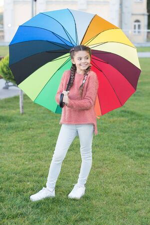 umbrella for little happy girl. Rainbow after rain. cheerful child. Spring style. Positive mood in autumn rainy weather. Little girl protected with colorful umbrella. Feeling protected at rainy day