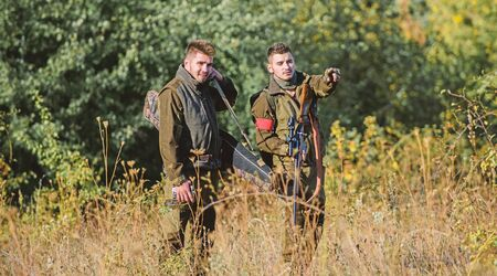 Illegal hunting. Hunters friends enjoy leisure. Hunters with rifles in nature environment.