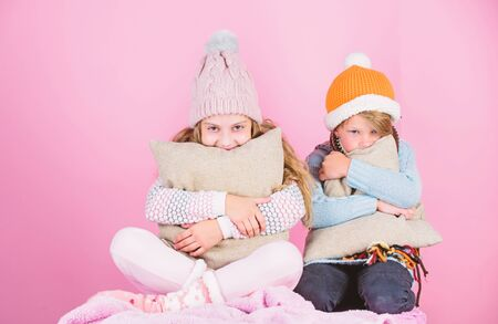 Siblings wear winter warm hats sit on pink Standard-Bild - 129262629
