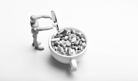 Wooden human dummy near cup full pills and tablets.