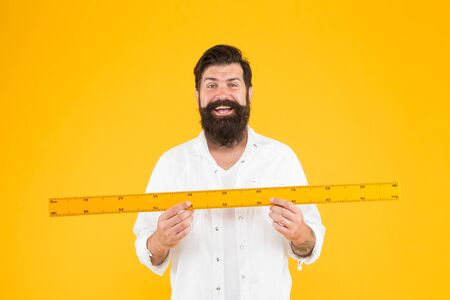 Happy teacher holding ruler on yellow