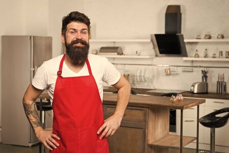 Bearded man in red apron.