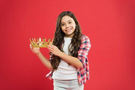 Little girl holding crown reward on red