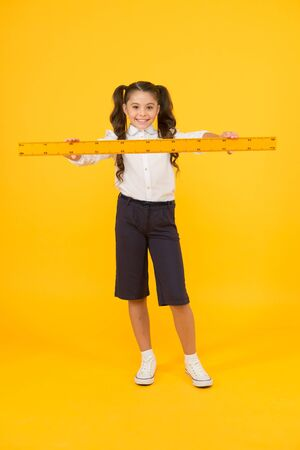 Pupil cute girl with big ruler. Banque d'images