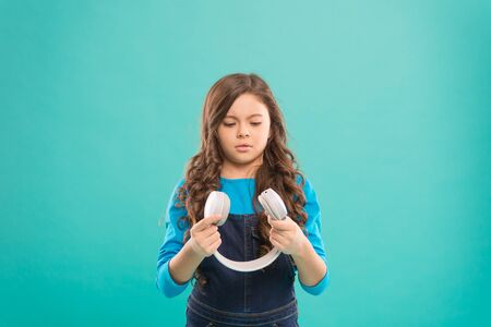 Little girl holding earphones on blue Stock Photo - 129262354