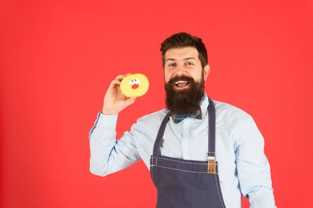 Professional cook holding doughnut on red Zdjęcie Seryjne