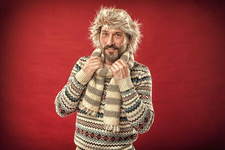 Bearded man accessorizing sweater with hat and scarf. Stock fotó