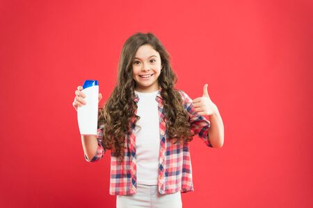Small child with wavy brunette hair showing thumbs up to gel on red Foto de archivo - 129262296