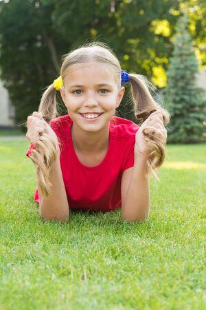 Girl cute kid laying green grass. Reklamní fotografie