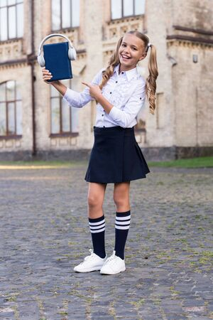 Girl cute schoolgirl hold book and headphones