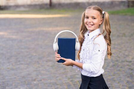 Girl cute schoolgirl hold book and headphones. Stock Photo - 129262283