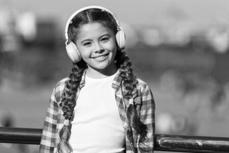Child listen music outdoors modern headphones.