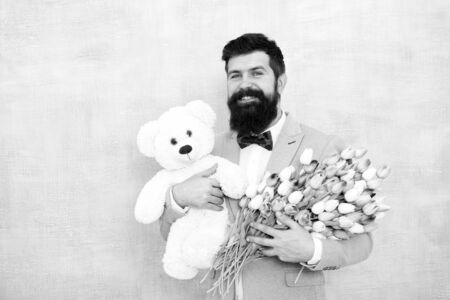 Bearded man in bow tie with tulip flowers