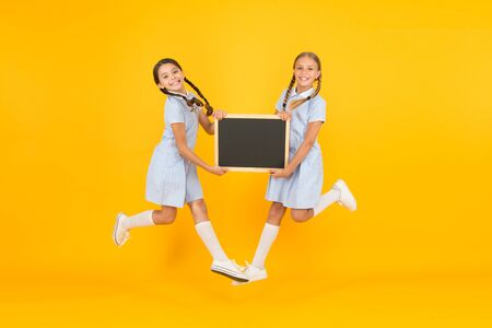 Small girls jump with blackboard.