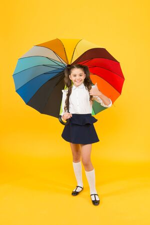 Everything under control. Fancy schoolgirl. Girl with umbrella. Rainy day. Happy childhood. Rainbow umbrella. Kid happy with umbrella. Fall weather forecast. Accessory for rainy day. Positive vibes.