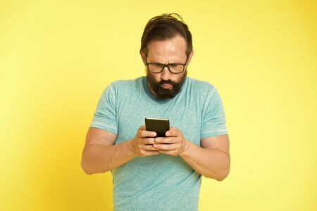Hipster puzzled use smartphone. Man inexperienced user of modern smartphone. Stay in touch with smartphone. Join online community. User friendly concept. Man puzzled mobile phone opportunities. 版權商用圖片