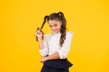 Modest hairstyle. Cute little schoolchild winding hairstyle around her finger on yellow background. Fashion girl with long ponytail hairstyle in formal style. Small kid styling hairstyle for school.