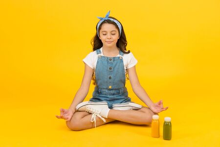 Vegetarian smoothie drink. Yoga training. KId girl sit meditate. Meditating practice. Good vibes. Peaceful meditating. Learn meditating techniques. Stay positive and optimistic. Healthy way of life.