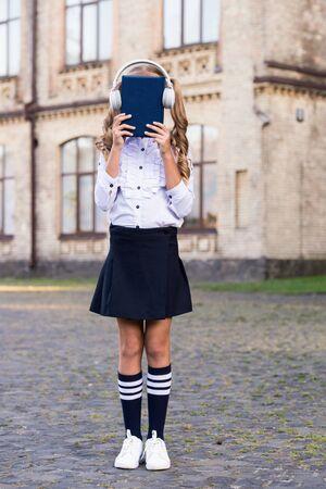 Girl cute schoolgirl hold book and headphones. Stock Photo