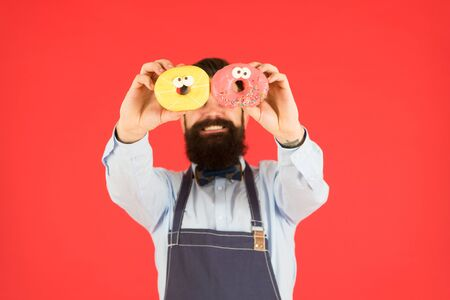 Fresh doughnuts selective focus after baking in hands of bearded man. Stockfoto