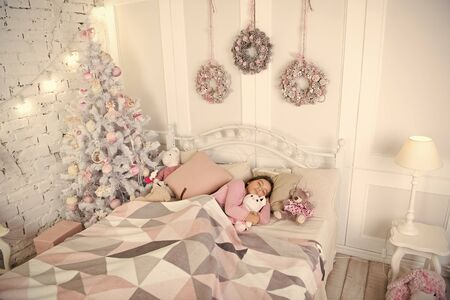 Girl little kid relaxing on bed light interior with christmas decorations. Christmas eve concept. Child waiting christmas in bedroom. Kid lay in bed relaxing. Home is the best place in the world