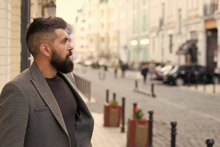 Catching taxi. Businessman catching taxi while standing outdoors urban background. Man bearded hipster casual style waiting for taxi. Guy at street city center. Looking for transportation. Bus stop Zdjęcie Seryjne