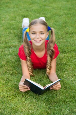 School time. Interesting stories for kids. Study with pleasure. Time for great stories. Little child reading book outdoors. Schoolgirl read stories while relaxing green lawn. Cute pupil enjoy reading
