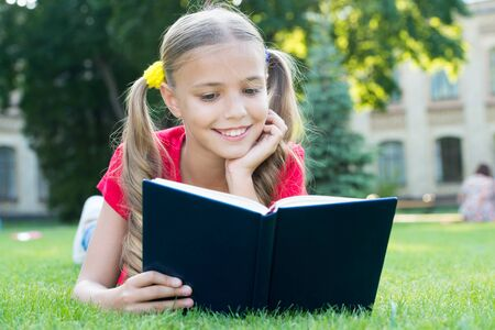 Schoolgirl read stories while relaxing green lawn. Cute pupil enjoy reading. School time. Interesting stories for kids. Study with pleasure. Time for great stories. Little child reading book outdoors Фото со стока