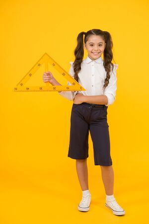 Triangle right angle. Math stem architecture faculty. Measuring equipment. Kid cute school student study mathematics. Knowledge day. Schoolgirl school uniform hold big ruler geometry school lesson Reklamní fotografie