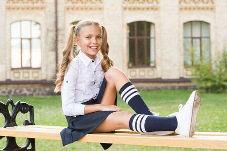 Pleasant minutes of rest. Time to relax and have fun. Relaxing in school yard. Perfect schoolgirl relaxing between classes. Life balance. Student adorable child in formal uniform relaxing outdoors