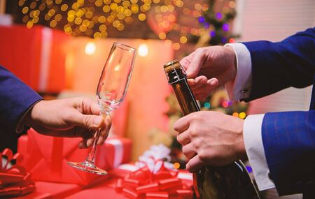 Drink champagne or sparkling wine. Celebrate new year with champagne. Last minute before new year. New year countdown. Hands opening champagne bottle and hold glass christmas decorations background
