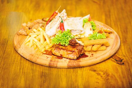 Snack for beer. Restaurant food. Wooden board french fries fish sticks burrito and meat steak served with salad. Pub menu snack. Enjoy your meal. Meat snack for group friends. Tasty delicious snacks