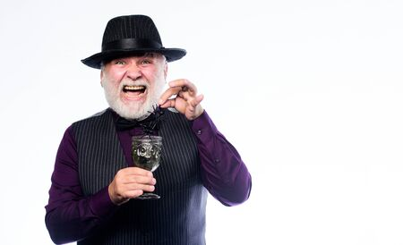 Halloween concept. Disgusting Halloween drink. Elegant bartender wear hat and vest prepare drink. Horror themed Halloween party. Weird old grandfather with gray beard. Add spider cocktail recipe