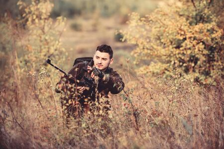 Man wear camouflage clothes nature background. Hunting permit. Hunting is brutal masculine hobby. Hunting and trapping seasons. Bearded serious hunter spend leisure hunting. Hunter hold rifle