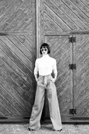 Femininity and emphasize feminine figure. Girl wear loose high waisted pants. Fashion shop. High waisted pants fashion trend. High waisted trousers. Woman attractive brunette wear fashionable clothes