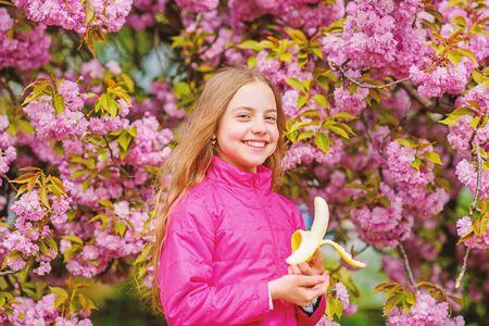Little girl eat banana. Kid on pink flowers of sakura tree background. Kid enjoying cherry blossom sakura. Happy spring vacation. Spring in botany garden. That is how spring smells. Tender bloom Imagens